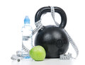 Big black fitness weight dumbbell with tape measure drinking water and apple on a white background healthy lifestyle loss Royalty Free Stock Photography