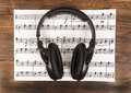 Big black professional headphones lying on the music sheet on the wooden background. Royalty Free Stock Photo