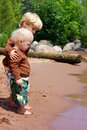 Big brother and baby on the beach a child is hugging protecting his as they stand near shore of a lake Royalty Free Stock Images