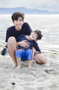 Big brother holding disabled boy on beach Stock Images