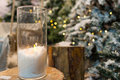 Big candles in glass vases in a snow-covered park or a forest while snowing Royalty Free Stock Photo
