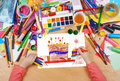 Big cartoon birthday cake child drawing, top view hands with pencil painting picture on paper, artwork workplace