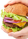 Big Cheeseburger Held in Hands Royalty Free Stock Images