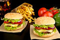 Big cheeseburgers on paper,french fries and glass of cola on black Royalty Free Stock Photo