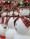 Big christmas snowman with red scarf and hat standing at the hat`s retail shop. Group of snowmen