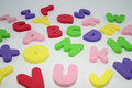 Big colorful letters alphabet made of foam on white background Stock Photos