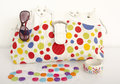 Big colorful polka dots bag with cute matching accessories summer on white shelf Stock Image