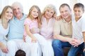 Big family portrait of senior and young couples with their children looking at camera at home Stock Image