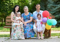 Big family sit on wooden bench in city park, summer season, child, parent and grandmother, small group of five people with balloon Royalty Free Stock Photo