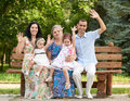 Big family sit on wooden bench in city park and waving, summer season, child, parent and grandmother, group of five people Royalty Free Stock Photo