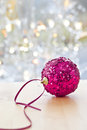 Big glittery christmas bauble in front of bright lights Stock Photos