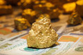 Big gold nugget and dollar bills Royalty Free Stock Photo