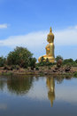 Big golden buddha statue sitting reflection on the water Royalty Free Stock Photo