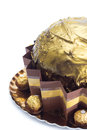Big golden cake with chocolates wrapped in paper on white background Royalty Free Stock Image