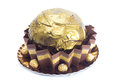 Big golden cake with chocolates wrapped in paper on white background Royalty Free Stock Images