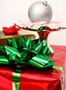 Big green christmas bow a large on a present with other holiday items in the background Stock Photos