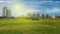 Big green field in front of residential buildings Royalty Free Stock Photo
