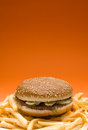 Big hamburger surrounded by french fries on orange background with copy space Stock Image