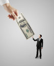 Big hand giving dollars money to businessman Royalty Free Stock Photos