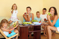 Big happy family eats fruit in cosy room Stock Photo