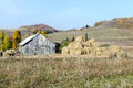 Big haystack near an old wooden shed against hills and the wood