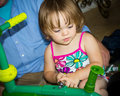 Big help two year old toddler girl helping to put her birthday present tricycle together Stock Photo