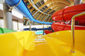Big indoor water slides in aquapark multi colored descent yellow slide Royalty Free Stock Images