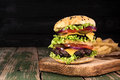 Big juicy hamburger with fried potato vegetables and beef on black wooden rustick background. Vintage toned