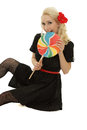 Big lollipop picture of young beautiful blond woman bit in the colored Stock Image