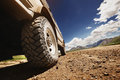 Big offroad car wheel on country road Royalty Free Stock Photo