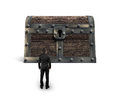 Big old treasure chest with small businessman looking at Royalty Free Stock Photo