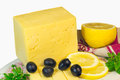 Big piece of cheese, lemon and olives on a white background. Royalty Free Stock Photo