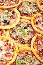Big pile of mini pizzas various forming a background Royalty Free Stock Images