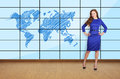Big plasma with map beautiful girl standing in office and Royalty Free Stock Images
