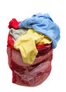 Big red mesh laundry bag overflowing with clothes isolated vertical shot of a Stock Photography