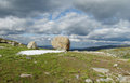 Big rocks on green mountain hill woth dark clouds on sky Royalty Free Stock Photo