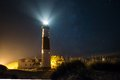 Big sable lighthouse at night with stars and light flashing Royalty Free Stock Image