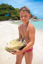 Big seashell held by a young boy on the beach Royalty Free Stock Photo