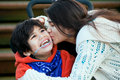 Big sister kissing disabled little brother  in wheelchair Royalty Free Stock Photo