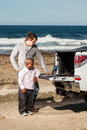 Big and small image of a dwarfish african men an young caucasian men standing behind a pickup truck working on a laptop Royalty Free Stock Photo