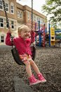 Big smile swing little girl swinging on a playground with a on her face Royalty Free Stock Images