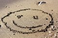 Big smiling face drawing in the sand Stock Photos