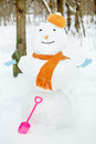 Big snowman in orange hat and scarf and in blue mittens stands in winter park plastic shovel is leaned to him Royalty Free Stock Image