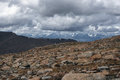 Big stones on the background of high mountain snow peaks ranges under cloudy gloom dark sky Royalty Free Stock Photo