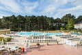 Big swimming pool view of a and nice with lots of deckchair in front of a forest of pine tree Stock Image