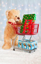 Big teddy bear with shopping cart and presents Royalty Free Stock Image