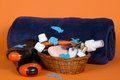 Big terry towel and basket with cosmetics on an orange background Royalty Free Stock Photos