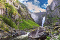 Big waterfall in the mountains, blue sky, green grass, summer Royalty Free Stock Photo