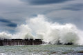 Big waves breaking on breakwater with stormy clouds Royalty Free Stock Images