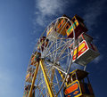 Big wheel closeup of at funfair with colorful boxes for passengers blue sky background Royalty Free Stock Image
